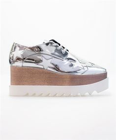 Alter nappa Oxford-style shoes in silver metallic featuring contrasting white star patches and a sustainable wood platform wedge with a chunky white rubber saw-edge or 'shark tooth' sole. Lace fastening with a squared off toe. 7.5cm heel with a 1.5cm platform