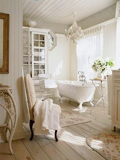 Elegant bathroom with vintage claw foot tub and rustic plank flooring. White beadboard walls and ceiling with crystal chandelier. Nickel tripod accent table, floral throw rugs, white glass front cabinet, gray paint color and upholstered chair.