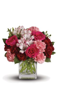 """Tickle her pink with this sweetly chic mix. Arranged in a modern cube vase, this bouquet blends hot pink and deep crimson roses with the delicate notes of alstroemeria and carnations. - Hot pink roses, red spray roses, pale pink alstroemeria and pink carnations are mixed with sprigs of fresh green oregonia - Delivered in a clear glass cube vase - Approximately 11 1/2"""" W x 11 1/2"""" H - Made in USA"""