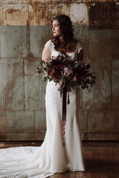 Overgrown fall-inspired bridal bouquet with deep red blooms   Image by The Colagrossis