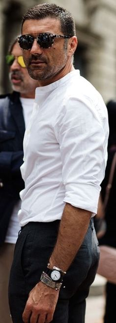Classic White Linen Shirt, Black Fitted Chinos, and Assorted Wrist Jewelry. Men's Spring Summer Street Style Fashion.