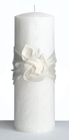 "This white eco-friendly palm wax unity candle stands 8.25"" tall.  A cream-colored satin ribbon wraps around the center of the candle and is accented by a cream satin rose and clear beads.Palm wax is an all-natural, sustainable renewable resource that is obtained from the oil palm in Southeast Asia. Palm wax is a superb material for making excellent burning candles and it resists melting in hot summer months.  Using palm wax is very similar to using traditional candle wax except there are no…"