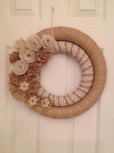 This handmade double wreath is wrapped in Burlap Cotton Ribbon on the outer ring and burlap and lace ribbon on inner ring. The finished size is approximately 15. It has been decorated with various burlap flowers. This wreath would make a wonderful addition to a front door or on any