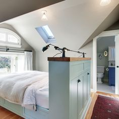 I really do love this attic bedroom with the bed facing the window and the storage in the headboard