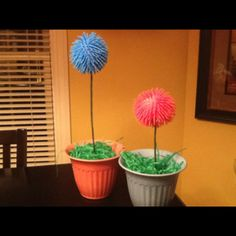 Dr. Seuss, Lorax movie Truffula trees made from squeeze toys.  Make a small hole in the toy which will deflate it.  Stuff it with cotton balls and put on the end of an artificial flower stem. Project cost 4$ total using items from the Dollar Tree.