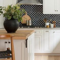 Black Fish Scale Tiles with White Cabinets