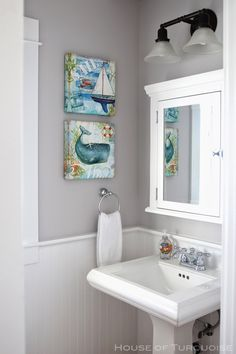 Light grey walls, wainscoting and pedestal sink