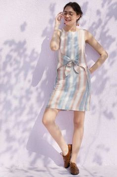 fe1bc87b6028 A minimalist  pastel toned sleeveless yarn dyed  stripes dress with a tie-up