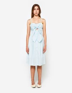 Feminine dress from Farrow in Blue. Adjustable thin straps. Sweetheart neckline. Adjustable tie at front with cutout detail below bust. Full-button placket. Tie closure at back. Pleats at waist. Flared skirt. On-seam side pockets. Straight hem. Lined  •