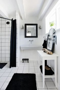 white tile with black/dark grey grout.  open shower. low ceiling/beams.