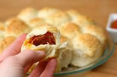 PIZZA BALLS! 3 cans Pillsbury Buttermilk Biscuits, 56 pepperoni slices, block of Colby cheese, 1 beaten egg, Parmesan, Italian seasoning, Garlic pwdr, 1 jar pizza sauce. Cut the block of cheese into 28 squares. Flatten a biscuit out and stack pepperoni and cheese on top. Gather up the edges of the biscuit. Line up the rolls in a greased 9x13 in. pan. Brush with beaten egg. Sprinkle with parmesan, Italian seasoning and garlic powder. Bake at 425°F for 18-20 minutes. **Use pizza sauce for…