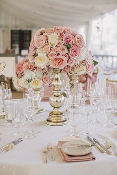 An arrangement similiar to this on columns to mark the space for the ceremony. I would have white and pink roses in a vase covered with navy and white striped cloth for the nautical look.