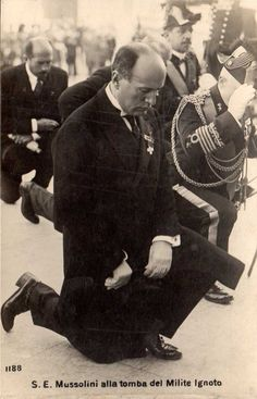 Benito Mussolini keeling at the graves of the unknown.