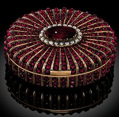 AN AUSTRIAN OR GERMAN JEWELLED GOLD SNUFF-BOX CIRCA 1850, UNIDENTIFIED MAKER'S MARK DK oval gold box, the hinged cover, sides and base applied with rows of graduating garnets radiating from, on the cover, a central garnet cabochon with seed-pearl border and on the base, an oval chased gold plaque with gold border within reeded gold mounts, polished gold thumbpiece