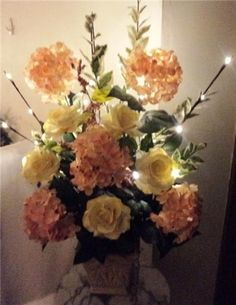 lighted branches in silk flower arrangement