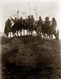 Crow Native Americans on horses, silhouetted on top of a Montana hill. 1908, Edward S. Curtis