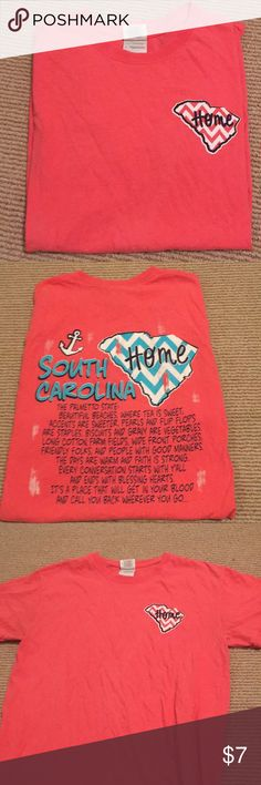 "South Carolina Home TShirt Pink/Coral South Carolina Home T-Shirt  The back reads ""The Palmetto State: Beautiful Beaches. Where tea is sweet, accents are sweeter, pearls and flip flops are staples. Biscuits and gravy are vegetables. Long cotton farm fields, wide front porches, friendly folks, and people with good manners. The days are warm and faith is strong. Every conversation starts with y'all and ends with blessing hearts. It's a place that will get in your blood and call you back…"