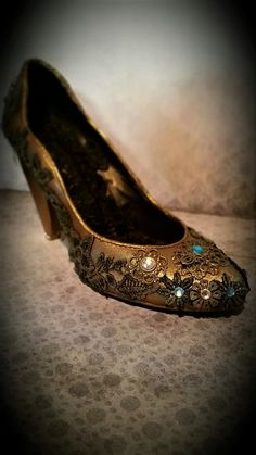 Altered high heel  shoe with lace, metallic paint, patina, metallic elements and rihnestones.