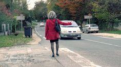 Autostoppeuse. Femme faisant de l'autostop sur une route de campagne. Vue de dos. Auto-stoppeuse habillée avec un haut rouge et une jupe courte noire.