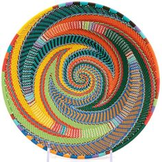 The past and the future are fused together in the creation of this beautiful basket, Zulu weavers have taken the intricate designs and incredible craftsmanship of their natural fiber baskets, and turned them into brightly-colored art from plastic-coated wire. Mesmerizing designs and vibrant colors are a hallmark of this functional art.