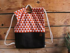 Comfortable and practical drawstring backpack! Easy to open and close, it can be carried as a backpack or on one shoulder only. Perfect for any occasion: urban, outdoors, school, you name it! To make it, I used : - dark brown leatherette - orange triangle cotton fabric - gray