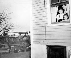 """The construction of Route 24, """"The Fall River Expressway,"""" lasted from 1950 to 1966. In 1952, construction of a portion of the highway was delayed due to Fall River brothers Jimmy (at left in the window) and Tommy Doherty, who had come down with the chicken pox. The family (the mother is identified only as """"Mrs. Raymond Doherty"""") was packed up and ready to move to allow for construction -- that's a bulldozer standing by to the left of the house -- but the family was permitted a respite until…"""
