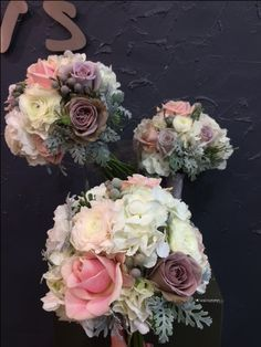 Beautiful bridesmaid bouquets with Amnesia, Sweet Avalanche roses, white ranunculus, silver brunia  berries, white hydrangea, silver leaves.