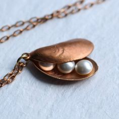 This amazingly detailed copper mussel shell consists of two sides which will lie against one another when worn. A modern take on the traditional locket. Nestled inside are a choice of either one, two or three tiny cream pearls! The mussel shell measures around one inch (25mm) long and is teamed with some perfectly matching copper chain. This necklace is available in a choice of lengths - please refer to my illustration for an idea of how these will look when worn.