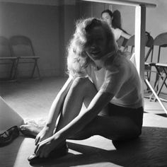 Norma Jeane (Marilyn) tying her shoes for a dance class.