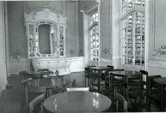 1974 - Bar do Teatro Municipal, com mesas e cadeiras de madeira escura. Ao fundo balcão todo trabalhado em relevo. Atrás uma prateleira de bebidas com um espelho ao centro. Portal de Acervos da Secretaria Municipal de Cultura