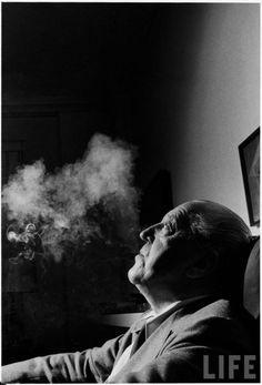 Portrait of architect Mies Van Der Rohe exhaling smoke.