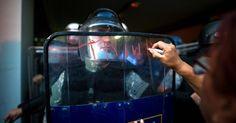 20160711 - Mulher escreve com batom em escudo de policial durante protesto contra o governo em Skopje, na Macedônia. O país está estagnado em uma crise política há mais de um ano, com acusações da oposição de que conservadores têm autorizado grampos de opositores Imagem: Robert Atanasovski/AFP