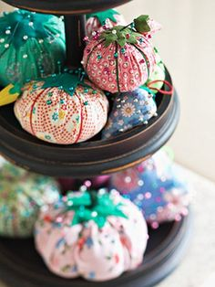 Cake stand with pincushions - - i bought a cute cardboard cupcake stand for my daughter's birthday, then reused it in my sewing room for smaller items that needed a home.