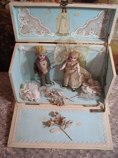 Boy and girl all-bisque dolls in a decorated box.