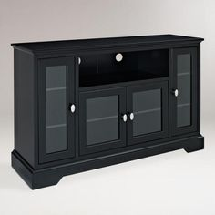Featuring adjustable shelves behind glass-paned doors, our sleek black TV stand offers plenty of storage for all of your media components and odds-and-ends. Black Tv Stand, Tv Unit Furniture, World Market Store, Cool Tv Stands, Black Wood, Adjustable Shelving, Entertainment Center, Man Cave, New Homes
