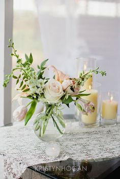Mix of wildflowers and garden roses in clear vase with pillar candles small-round vase