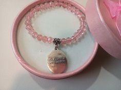 """Detalle para niñas en su primera comunión, es una pulsera elástica con bolitas de cristal rosa y colgante plateado de """"mi primera comunión"""""""