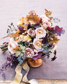 """""""My favorite palette is lavender with chocolate and copper,"""" says Gill. The below bouquet runs the gamut of his choice shades, with purple kale and salvia buds, black chervil, lavender garden roses, marbled coralbell leaves, and gilded acorns and oak leaves. Despite the large range of blooms, """"the small clutch is special but not fussy,"""" he says."""