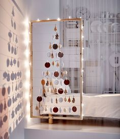 A side of an IVAR storage unit is used as a large frame for a DIY Christmas tree made from holiday ornaments.