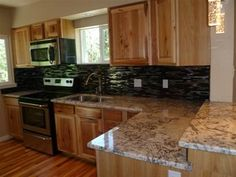 black backsplash, white granite countertops- the look I think I'm going for, but our cabinets are a dark reddish brown.