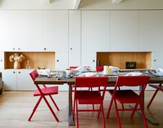 The red Piana folding chairs are by David Chipperfield for Alessi; Garneau custom-designed the millwork tabletop and stainless-steel legs.