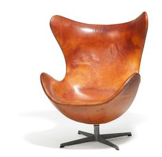 "Arne Jacobsen // ""The Egg Chair"". Early easy chair with profiled aluminum base. Seat, sides and back upholstered with original, patinated cognac coloured leather. Model 3315. Designed 1958. This example manufactured circa 1960 by Fritz Hansen."