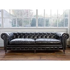 Beautiful black Chesterfield sofa. While this would probably dominate a studio apartment...what a thing to be dominated by, yes?