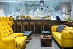 BoHo-chic canary yellow Chesterfield sofa sings in this upscale London bar.