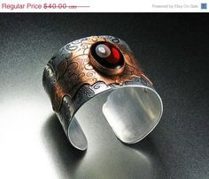 Stainless steel and copper etched cuff with a red glass jewel.