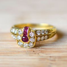 18 karat yellow gold ring with an oval ruby and three princess cut rubies at 0.28 carat total weight and 19 round diamonds at 0.48 carat total weight VS clarity G-H color, circa 1950. Size 7.