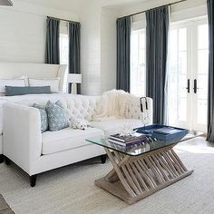 White Wingback Bed with Blue Curtains