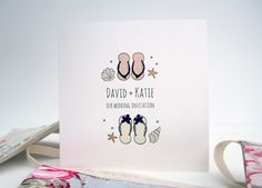 'Beach Wedding' wedding invitation featuring boy and girl flip flops with beach shells and starfish. Perfect for a wedding abroad on here in the UK on the beach or by water.