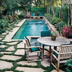 Natural Pool Oasis.This space is a shining example of how water features and gardens can work well together. A long, narrow, rectangular lap pool is set into the middle of the yard. The shape provides plenty of room for swimming, while the location makes it the centerpiece of the design. Dark ribbons of dwarf mondo grass fill the cracks between flagstones. The mondo grass creates a cooler, less reflective surface and reinforces the natural-looking appearance of the space.
