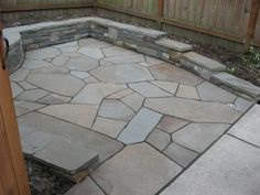 tidy seat/retaining wall, patio of irregular bluestone shapes, but smooth, even surface